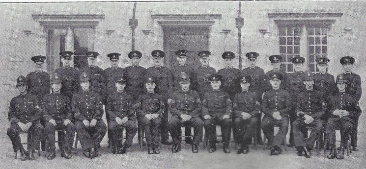 Gloucester Urban Division Hopewell Street Section. Back row: Special Constables Collier, Hobbs, Wheeler, Head Special Constable Peacey, Special Constables Carpenter, Drinkwater G, Hubbard, Jones, veal, head Special Constable Cresswell, Special Constables Embling, Langley, Drinkwater W Smith. Seated: Police Constables Tilling, Kitteringham, Simmonds, Police War Reserve Bundy, Special Sergeant Hobbs, Police Sergeant Ryland,  Special Sergeants Baldwin, Ilott, Police War Reserve Green, Police Constables Trowbridge, Drenan (Gloucestershire Police Archives URN 7011)