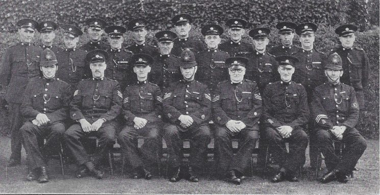 Gloucester Rural Division Hucclecote Section. Back row: Special Constables Wasley, Lane, Cole, Stone, Freeman, Jones. Middle row: Special Constables Bick, Hardman, Mann, Lane, Cooper, Hayward, Betteridge, Meyers. Seated: Police Constable Baker, Special Sergeants Richmond, Kent, Police Sergeant Cooper, Special Sergeant Newman, Special Constable Payne Police Constable Clarke. (Gloucestershire Police Archives URN 7012)