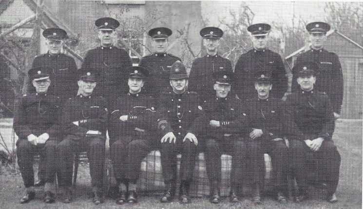 Forest of Dean Division Longhope Section. Back row: Special Constables Bowkett, Hill, Warren, Constance, Little, Bullock. Front row: Special Constables Morris, Adams, Head Special Constable Jones A.H, Police constable James, Special Constables Lord, Williams, Poole. (Gloucestershire Police Archives URN 7017)