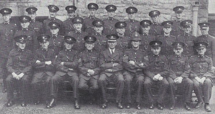 Forest of Dean Division Lydney Section. Back row: Special Constables Windsor, Davis, Goddard, Hadley R, Hadley H, Imm, Martyn, Bayliss, Garland. Middle row: Special Constables Ball, Gibson, Hancock, Waters, Bailey, Wright, Seaborne, Miell, Born. Seated: Special Constables Dunn, Williams, Nelmes, Special Sergeant Wild, Superintendent Large, Police Sergeant Clarke, Special Constables Morris, Thorn (Gloucestershire Police Archives URN 7018)