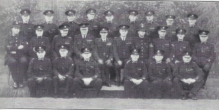 Stroud Division Painswick and Whiteshill Section. Back row: Special Constables Dorsett, Eaton, Keene, Taysum, Feltham, Ryland, Garner, Sprig, Hill. Middle row: Police Constable Pitfield, Head Special Constable Croome  Special Inspector Bendall, Superintendent Williams, Commandant Sleeman, Special Superintendent Limbrick Police Sergeant Goddard, Head Special Constables Dearlove, Baker. Front row: Special Constables Tidmarsh, Scrivens, Gyde, Hughes, Daniels, Avery. (Gloucestershire Police Archives URN 7025)