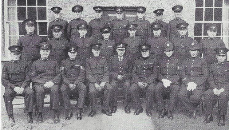 Forest of Dean Division Parkend Section. Back row: Special Constables James E, Dawe, Cawley, Hook, Edmunds, Sheward, Turley W. Middle row: Special Constables Brown, Morgan, James S, Bethell, Davis, Turley H, Goldsworthy, Jessop. Seated: Special Constable Turley, head Special Constable Rossiter, Special Sergeant Pudsey, Special Inspector, Machen, Superintendent Large, Inspector Dowsell, Police Sergeant Pagett, Police Constable Carter, Special Constable Thomas.(Gloucestershire Police Archives URN 7026)