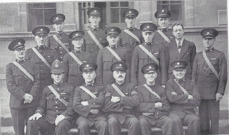 Cheltenham Urban Division  Shurdington Section. Back row: Police War Reserve Nicholls, Special Constables Biggs, Senington, Welch. Middle row: Special Constables Jenkins, Ross, Joynes, Bliss, Drake, Griffiths, Cole. Seated: Police Constable  Greenslade, Head Special Constable Child, Special Sergeant Hewinson, Head Special Constable Sansom, Special Constable Haidon.(Gloucestershire Police Archives URN 7031)