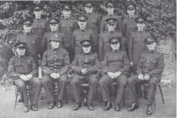 Forest of Dean Division St Briavels Section. Back row: Special Constables Scrivens, Lewis, Davies, James, Davis. Middle row: Special Constables Voyce, Keedwell, Price, Burley, Whittington. Seated: head Special Constable Morgan, Police Constable Day, Inspector Dowsell, Special Constable Rivers, Police War Reserve Henderson.(Gloucestershire Police Archives URN 7032)
