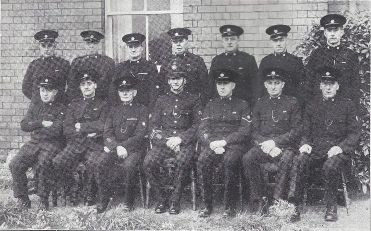 Forest of Dean Division Westbury on Severn Section. Back row: Special Constables Leaper, Wyman, Smart, Heaven, Jennings S, Gleed, Price. Seated: Special Constables Littleton, Jennings, Selwyn, Police Constable Cook, Head Special Constable Boughton, Special Constables Wyman, Middlecote (Gloucestershire Police Archives URN 7037)