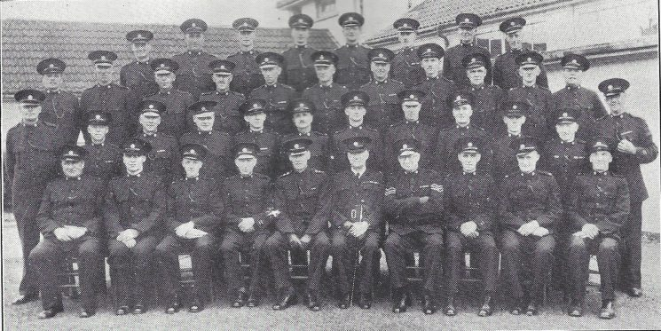Forest of Dean Division Coleford Subsection. Back row: Special Constables Smart, Jefferies, Smith S.L.H, Joseph, Holbrook, Smith E.W, Brain, Baldwin. Third row: Special Constables Hart, Collett, Williams J.E, Phipps, Morgan, Higgs, Miller, Pritchard, Jones R.I, Gwilliam, Baldwin. Second row: Special Constables Saunders, Barnett, Hooper, Baynham, Burbrough, Bucknell, Jones F.W, James, Smith H.H, Trotter, Williams W.F, Dangerfield Seated: Special Constables Green, Powell, Homer, Head Special Constable Ashworth, Special Inspector Machen, Special Superintendent Colchester- Wemyss, Special Sergeant Pudsey, Head Special Constable Horton, Special Constable Dovey, Hoare.(Gloucestershire Police Archives URN 7040)