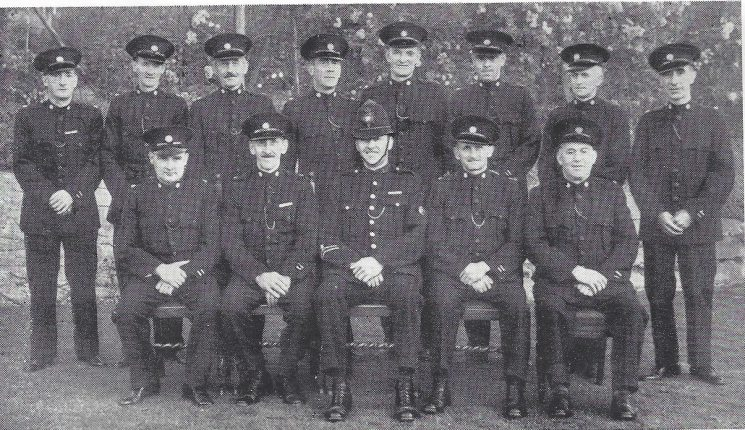 Forest of Dean Division Drybrook Section. Back row: Special Constables Terrett, Cinderey, Morman E, Shirley, Blears, Roberts G, Roberts M.T, Greening Seated: Special Constable Collier, Head Special Constable Morman T.D, Police Constable Rogers, Special Constables Annetts, Hunt. (Gloucestershire Police Archives URN 7041)