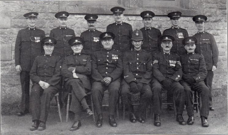 Moreton in Marsh Division Guiting Power Section. Back row: Special Constables Reynold, Smith, Lovesey, Garland, Hunt, Coldicott, Holloway. Seated: Special Constable Chesters, Special Inspector Wellesley, Inspector Hallam, Police Constable Wroot, Special Sergeant Ross Willis, Special Constable Beard.(Gloucestershire Police Archives URN 7045)