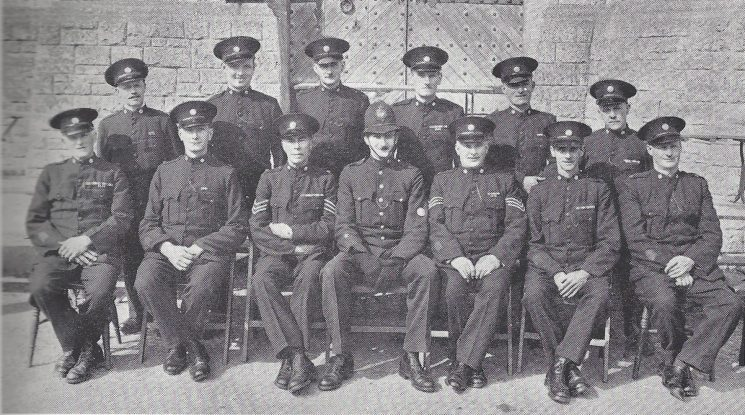 Cirencester Division Daglingworth Section. Back row: Special Constables Locke, Smith J.J. Ripley, Smith R.W, Fawkes, Tokelove. Seated: Special Constables Howick, Payne, Special Sergeant De Freville, Police Constable Holtham, Special Sergeant Short, Special Constables Clarke, Harvey. (Gloucestershire Police Archives URN 7049)