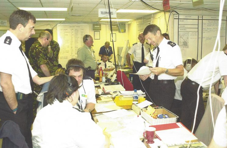 Building 1223 at Fairford 2002. Chief Inspector Ian Clark, Chief Superintendent Adrian Grimmett, Police Constable Bob Holdsworth wearing headphones, Liz Browning and Sergeant Chris Williams. This is what would now be called Silver Control. (Gloucestershire Police Archives URN 8045)