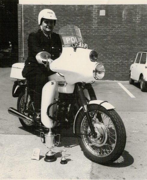 Police Constable  Brian Bailey on 650cc Triumph Saint WDF 17J, in June 1971. This was just after the Auto Cycle Union National Rally, which is a rally style event that requires riders and teams to plan a route to check-in to a maximum number of control points, with a minimum of miles covered and get an award - Gold, Silver or Bronze accordingly. Control points open at midday on a Saturday and  competitors have to check-in at the finish point, which for many years including 1971 was located at Trentham Gardens, Stoke on Trent, at the earliest at 0600hrs  Sunday morning and no later than 0800hrs. In the 1960s and 1970s many Forces participated in this event. In 1971 Brian was the Top Service rider, receiving a handsome gold (plastic) cup. (Gloucestershire Police Archives URN 8188) | Photograph from Wendy Davenport