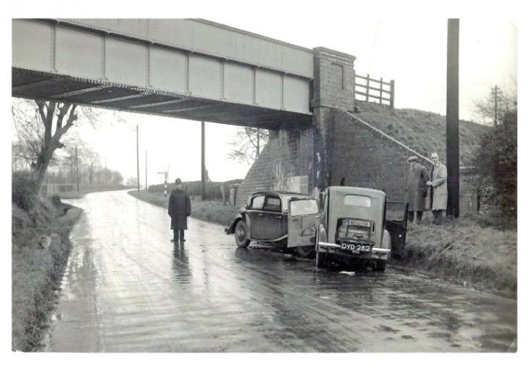 Under the railway bridge Fosseway Bourton-on-the-Water . Note the police officer standing under the bridge so he doesn't get wet. Picture is Lansdown looking north towards Stow-on-the-Wold. (Gloucestershire Police Archives URN 8914)