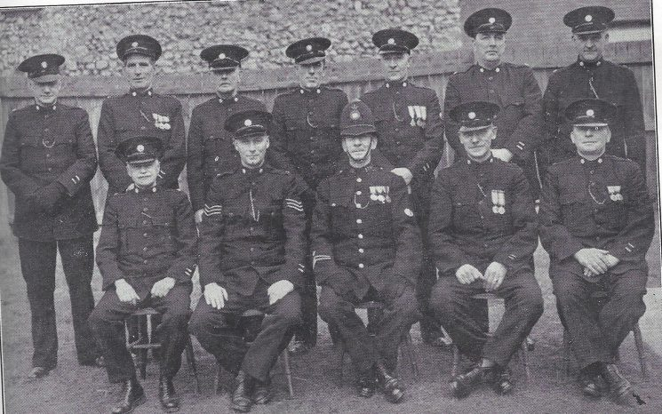 Cheltenham Urban Division  Prestbury Section. Back row: Special Constables Lee, Brookes, Harrison, Newman, Brockman, Gurney, Short. Seated: Special Constable McNeale, Special Sergeant Ward, Police Constable Lodge, Special Constables Preece, Stokes. (Gloucestershire Police Archives URN 7027)