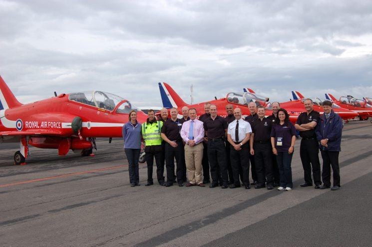 Joint Gloucestershire, Wiltshire and  Royal International Air Tattoo Silver Control and Ground commanders team pose with the Hawks of the Red Arrows team. All Gloucestershire unless it says otherwise. Amber Meek, Jerry Foster-Turner, Andy Ewans, Gary Thompson, Kev Roseblade, Nick Cook (Royal International Air Tattoo Security), Tony Scragg , Marcus Griffiths, Rob Priddy, Ian Phillips, Tony Godwin, Mark Levitt - Wiltshire, Ian Copus - Wiltshire, unknown staff member - Royal International Air Tattoo, Nick Ashley - Wiltshire, Peter Tocknell. (Gloucestershire Police Archives URN 9018) | Photograph from Kevin Roseblade