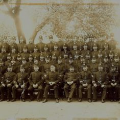 Sepia group photo of officers, mainly Constables with a Superintendent and 2 possible Inspectors - may be a Divisional group. Collar numbers visible:  24 Thomas James, 40 Charles Bullock, 41 Jesse Sollars, 45 William Dance, 67 Frederick Gardiner , 83 Charles Poulton, 86 Frederick Carter, 103 Walter Windsor, 105, 118 Jabez Iles, 147 Alfred Holmes, 162 Francis Nash , 220 Henry Newland, 233 Morton C White , 265 Albert Gosling, 285 John York, 294 George Jordan, 312 George Clutterbuck, 335? Albert Green 171 Charles Davis. (Gloucestershire Police Archives URN 1657)