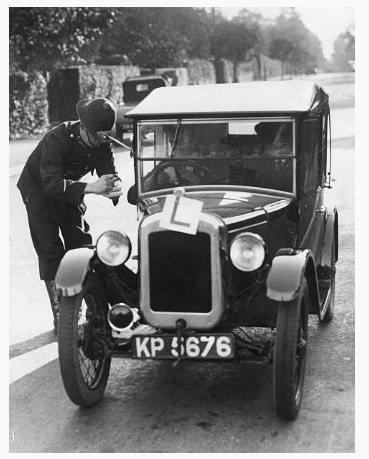 A policeman checking that a learner driver in Cheltenham,  has current car tax.Photograph taken October 3rd  1935. The photograph was taken on the London Road at Six Ways between Holy Apostles and the London Inn. (Gloucestershire Police Archives URN 9213)