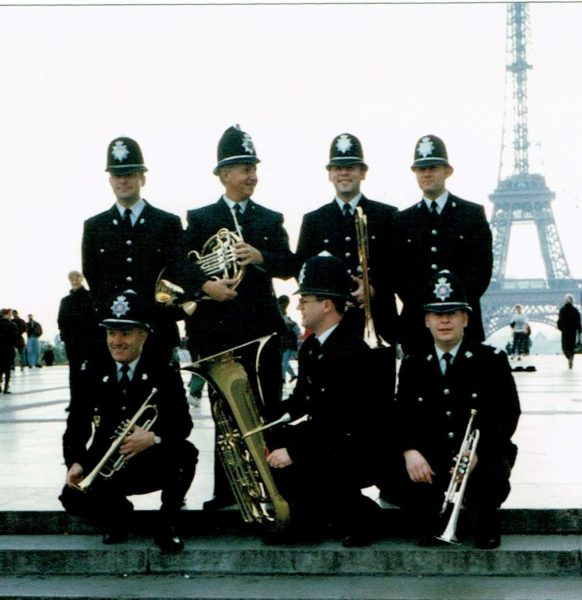 In order to promote the concerts, a brass quintet in full British police uniform, went out into the city to play to the public, and included performances under the Eiffel Tower, and at the Pompidou Centre. We had taken uniforms but had not considered permission to play, so as soon as we started at the Eiffel Tower, the local Gendarmes appeared to inform us we had no license to play and therefore had to stop. A short conversation led to them changing their mind – as we were not collecting any money, they would 'walk round the block' and be back in half an hour, and we would then have to stop!! We walked around Paris and travelled around the Metro with instruments, in uniform. And found it was a very easy way to confuse American tourists!! Back row – Alec Cane (Cheshire), Roger Barker (Staffordshire), Neil Davies (South Yorkshire), Gerard Valentine (Greater Manchester Police) Front row – John Morgan (Dyfed Powys), Trevor Moss (Gloucestershire), Ric Hewin (Dorset) (Gloucestershire Police Archives URN 9658) | Photograph from Trevor Moss