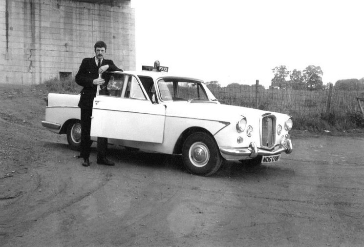 John Bryant with one of the last of the Wolseley  6/110 patrol cars, here seen underneath the Severn Bridge. (Gloucestershire Police Archives 10022) | Photograph from John Bryant