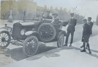 Main Street Chipping Sodbury 1921. This car was thought to be a present from his mother, Eliza,  on his promotion to Superintendent.The car cost £100. In the car his wife Olive and also pictured his sons Joseph Lovell Goulder 15 and  George Edward Goulder 12. The photograph was taken outside Hartley House where they lived in the main street in Chipping Sodbury. (Gloucestershire Police Archives 10034)