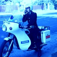 """This is """"Petrol Pete"""" Maunder, on a Triumph 650cc Saint. At this time the Traffic motorcyclists, as opposed to the riders of the 250cc beat bikes, were issued with helmets with an integral ear speaker and boom mike. This was probably  a publicity shot, showing """"the old way"""" when the rider had to stop to transmit and  of course the new, super improved way, when he rode past the camera, happily chatting to Information Room. (Gloucestershire Police Archives URN 10347) 