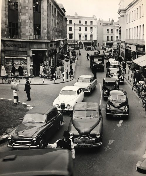 Directing traffic in Cheltenham. The roundabout contains the fountain that is on Boots Corner. Dodwells is in the space now occupied by Starbucks and Manns jewellers. The gap between the shops in the top right hand part of the photograph is Post Office Lane. (Gloucestershire Police Archives URN 10464)