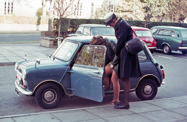 "Early 1970s when the uniform for Women Police Constables changed. This is Sue Dawkins (then Sue Wakefield) bringing in a prisoner. The ""prisoner"" was a member of the typing pool. The women's department had a mini as their department vehicle. (Gloucestershire Police Archives URN 10727) 