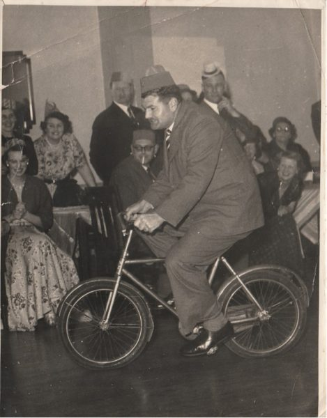 Police Constable   Newman  riding a bicycle at a social event perhaps Christmas party looking at the hats. (Gloucestershire Police Archives URN 10746) | Photograph from Jenifer Hone