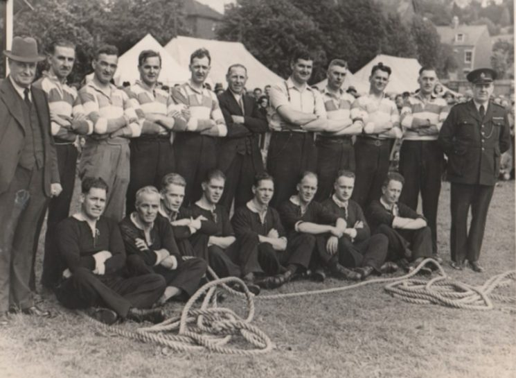 1946 Tug of war teams Back row left to right: Superintendent Soldier, Harry Thomas, unknown, V Batstone, Morris, H Olpin, W Newman, A Savage, I Dimery, unknown, J Halllam. Front Row left to right : Williams, W Workman, Newman, King, R Sandle, H (Harry) Gribble, unknown, A Tucker, F Taylor. This is believed to have been taken at the first constabulary sports day after World War ll this was held at The Wagon Works. (Gloucestershire Police Archives URN 10750) | Photograph from Jenifer Hone